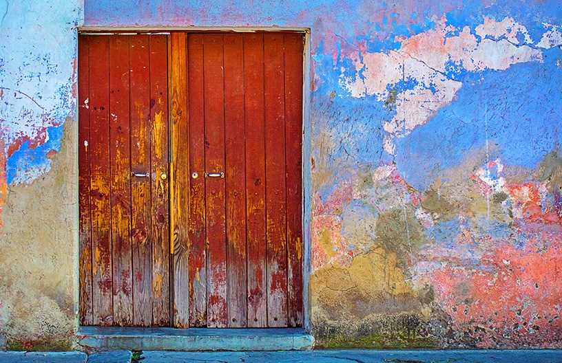 Closed rustic red door within a wall that is colourful yet aged