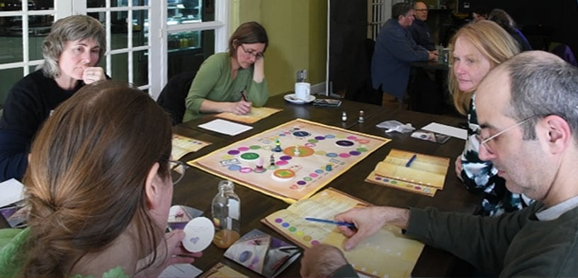 A group of people are gathered around an Exit Matters game, deep in thought